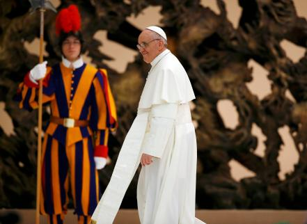 Pope Francis I passes a Swiss Guard as he leaves the Paul VI hall after an audience for members of the media, at the Vatican